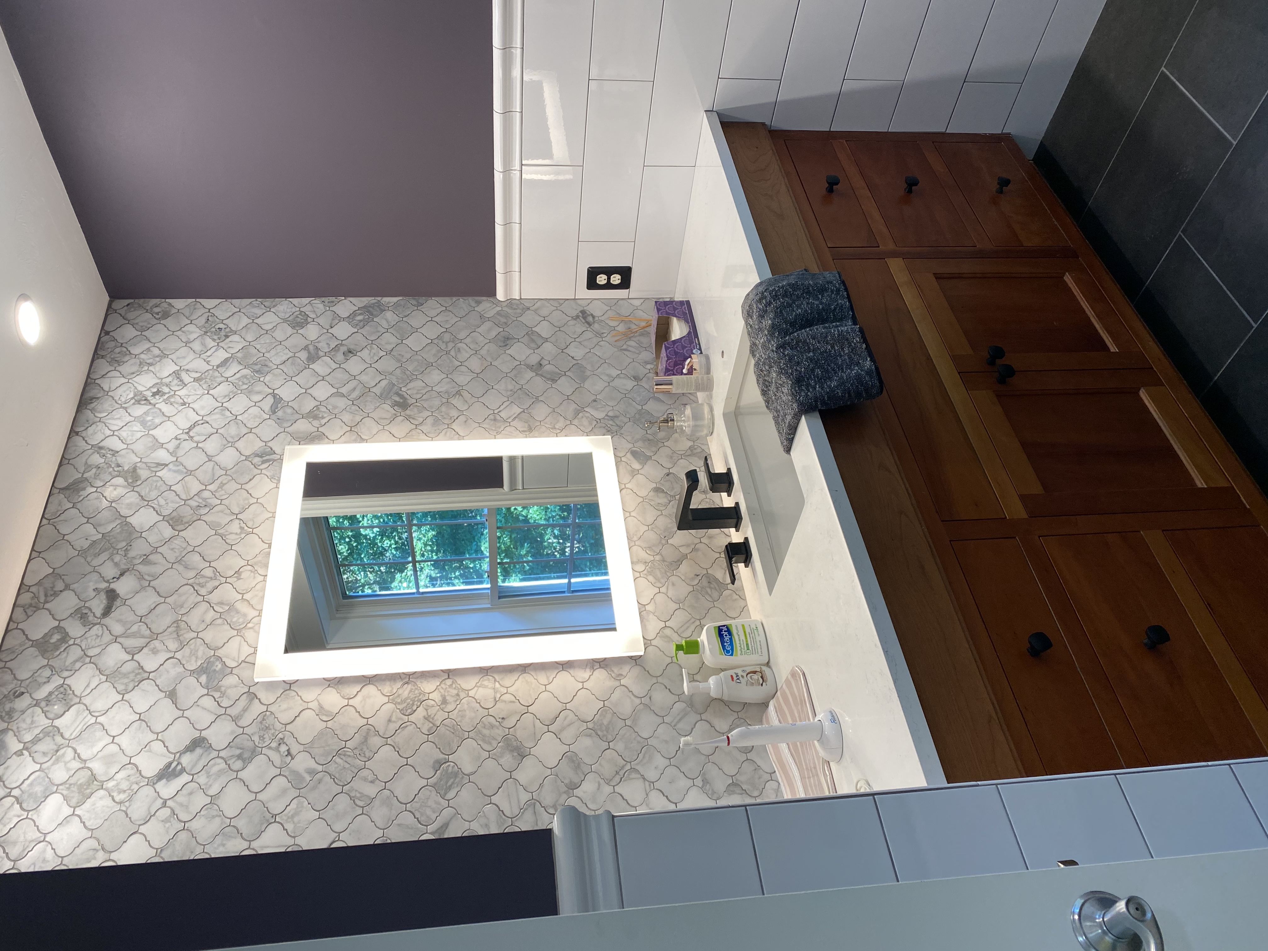 A recent bathroom remodel featuring an arabesque tile backsplash, glossy subway tile half-wall, and dark tile on the floor.